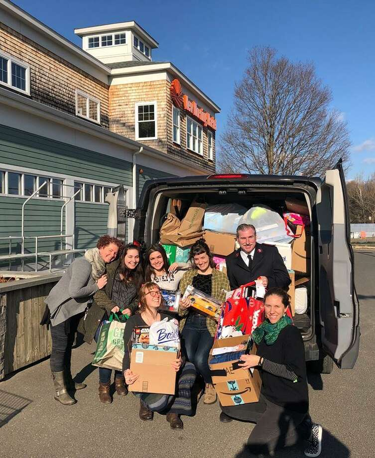 New Morning Market staff help load hundreds of gifts into the Salvation Army's van. Photo: Contributed Photo