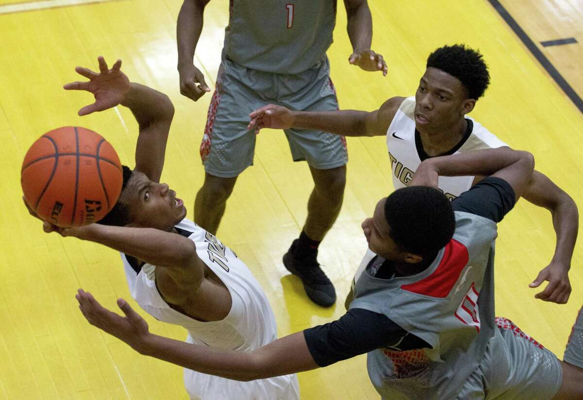 Conroe guard Michael Phoenix (3) goes up for a rebound against Westfield forward Elijah Lee (4) during the fourth quarter of a non-district high school basketball game at Conroe High School, Tuesday, Dec. 4, 2018, in Conroe.