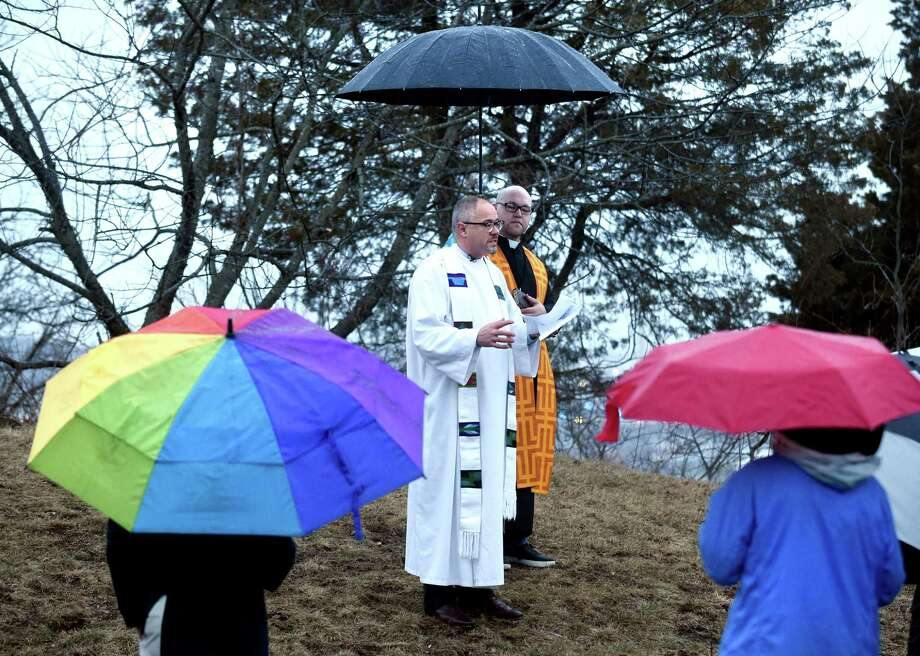 Rev. Edwin Perez, Jr. (right), Minister for Social Justice at the United Church on the Green in New Haven, holds an umbrella for Rev. Paul Fleck, Pastor of Hamden Plains United Methodist Church in Hamden, during an Easter Sunrise Service at the summit of East Rock Park in New Haven on April 1, 2018. Photo: Arnold Gold / Hearst Connecticut Media / New Haven Register