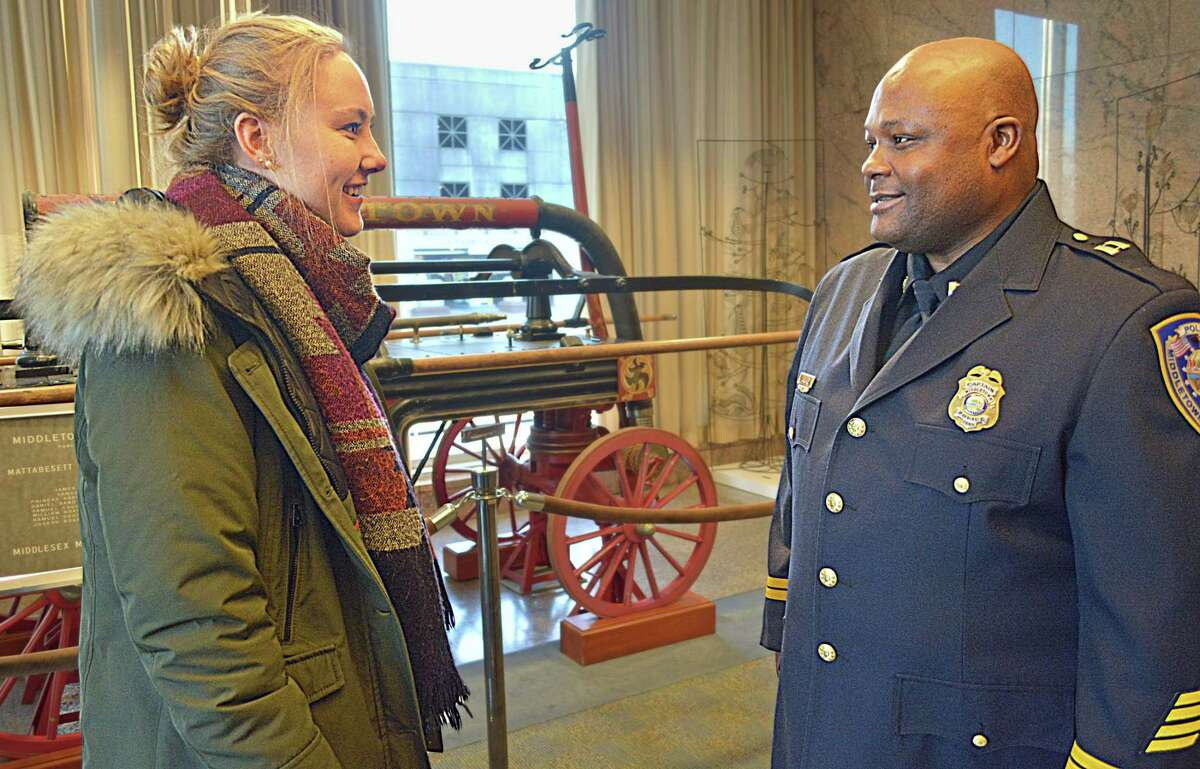 Middletown police intern Charlotte Schroeter of Wiesbaden, Germany, left, speaks to Capt. Gary Wallace following a promotional ceremony for four officers at Middletown City Hall Dec. 7.