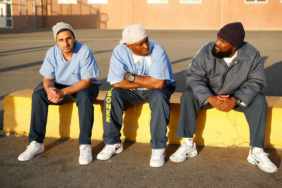 San Quentin inmates Adnan Khan, left, Shadeed Wallace-Stepter, center and Earlonne Woods are seen on the yard on June 27, 2018. Wallace Stepter and Woods have since been released from prison and are going through the Re:store Justice re-entry program in Oakland, Calif.