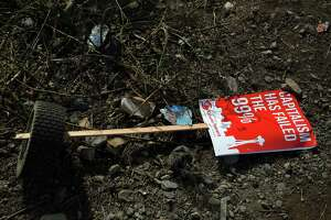 "A sign from city council member Kshama Sawant's socialist group reading ""Capitalism has failed the 99%"" lies on the ground in a homeless encampment under the Ballard Bridge in Seattle. Has socialism been discredited? Not so fast."