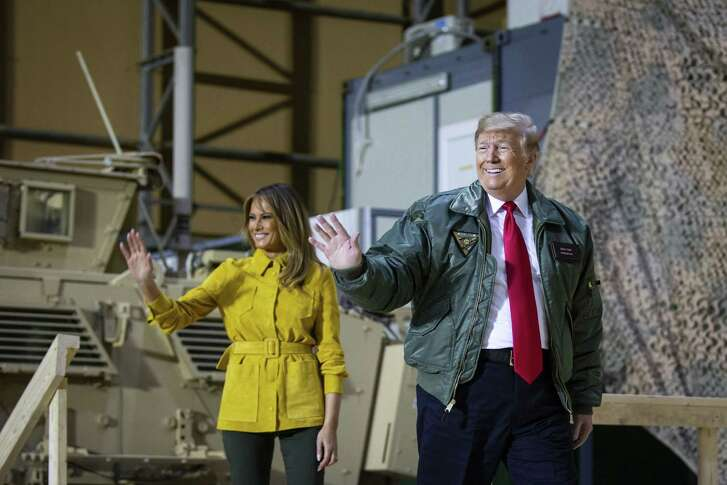 President Donald Trump and first lady Melania Trump enter a hangar to meet military personnel at the al-Asad Air Base in Iraqs Anbar province, Dec. 26, 2018.