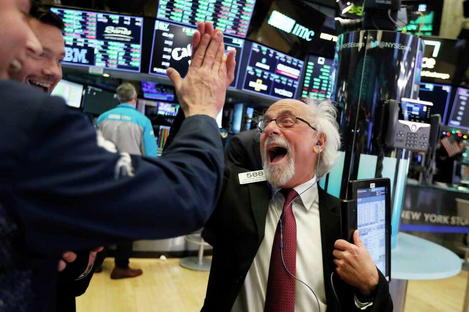 Traders Peter Tuchman, right, slaps a high five before the closing bell on the floor of the New York Stock Exchange, Wednesday, Dec. 26, 2018. The Dow closed up more than 1,000 points in best day for Wall Street in 10 years as stocks rally back from Christmas Eve beating.(AP Photo/Richard Drew) Photo: Richard Drew / Copyright 2018 The Associated Press. All rights reserved