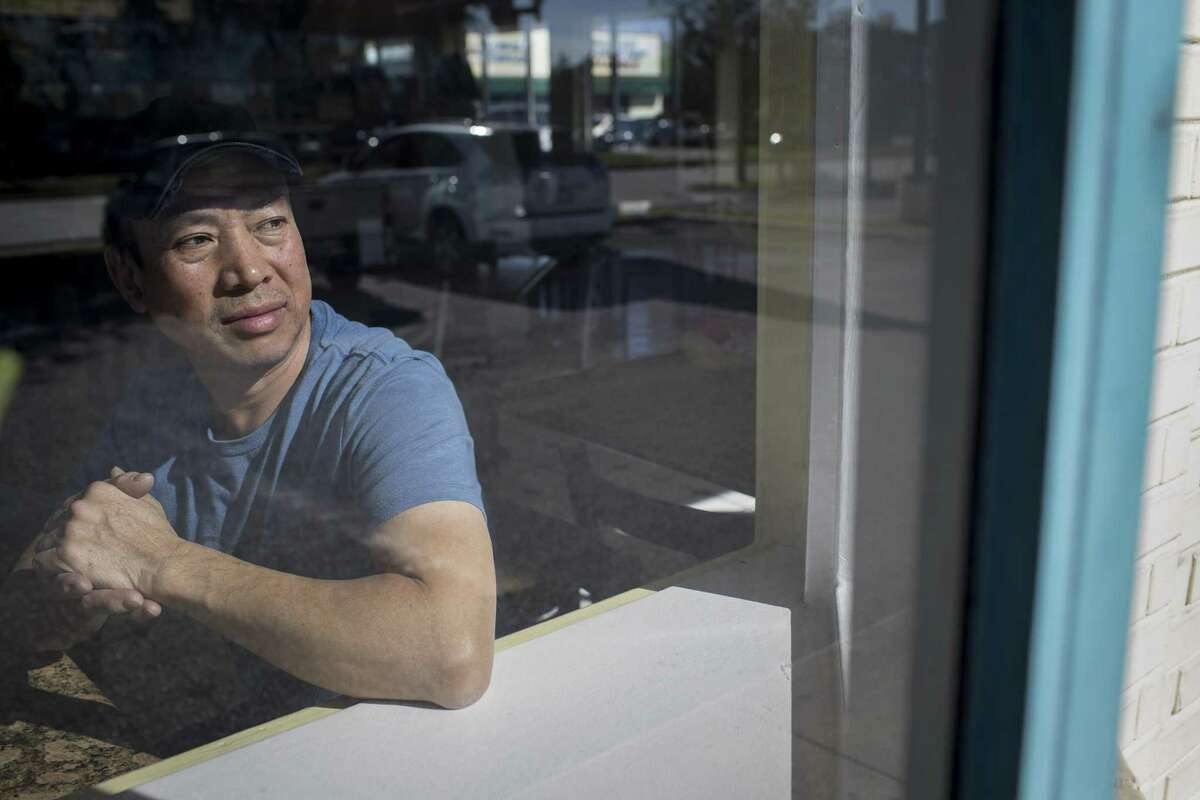 Kevin Khong, who own's Don's Cafe and Sandwiches in the Chinatown area, said some of his customers have been reluctant to contact police after robberies. Khong looks out onto his parking lot, Tuesday, Dec. 4, 2018, in Houston.