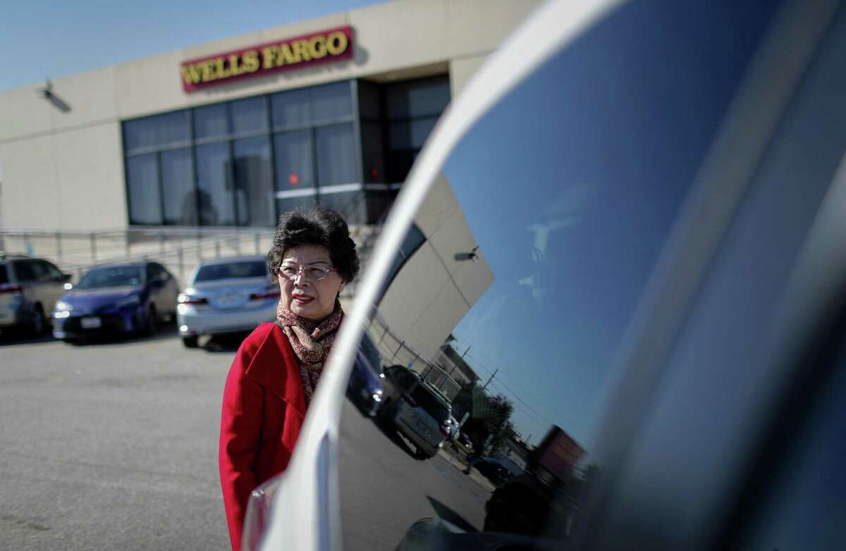 Li-Shen Kline, a real-estate broker who is working to increase safety and security in the Chinatown area, looks over her shoulder in the parking lot of a bank where her car was previously broken into, Tuesday, Dec. 4, 2018, in Houston.