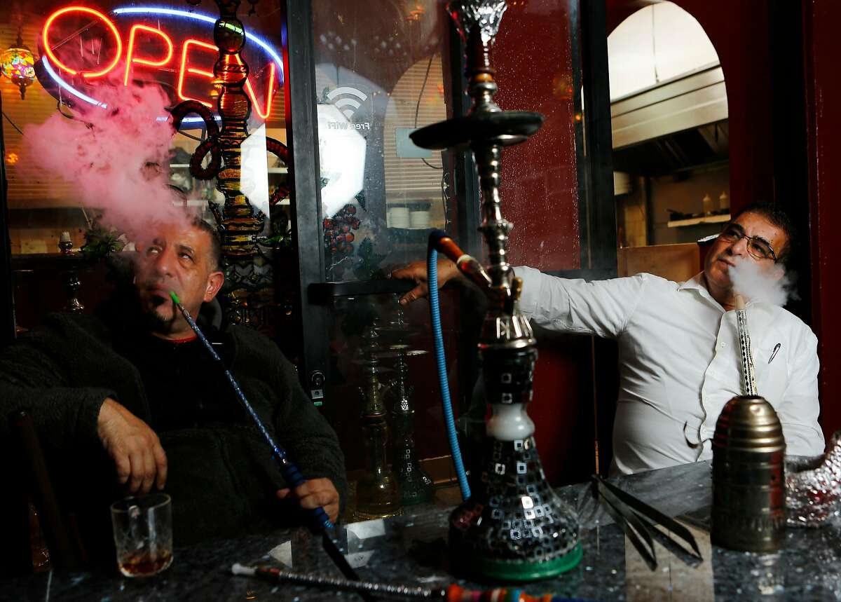 From left: Khaled Shehadeh and Adnan Abu Sharkh smoke hookah at Pride of the Mediterranean on Tuesday, Nov. 27, 2018, in San Francisco, Calif. Sharkh is the owner of the hookah lounge and restaurant, which is located at 1761 Fillmore St.