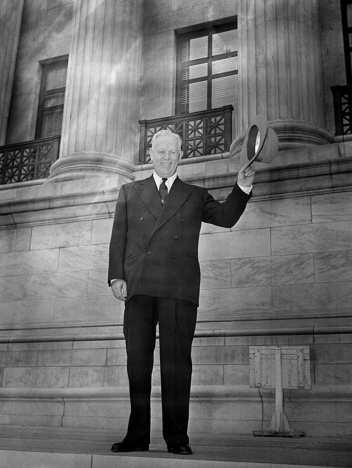 Earl Warren smiles and waves while standing at the base of the two pillars of the Supreme Court building in Washington, D.C., Oct. 5, 1953 after arriving to become the 14th Chief Justice of the United States. (AP Photo/Henry Griffin)