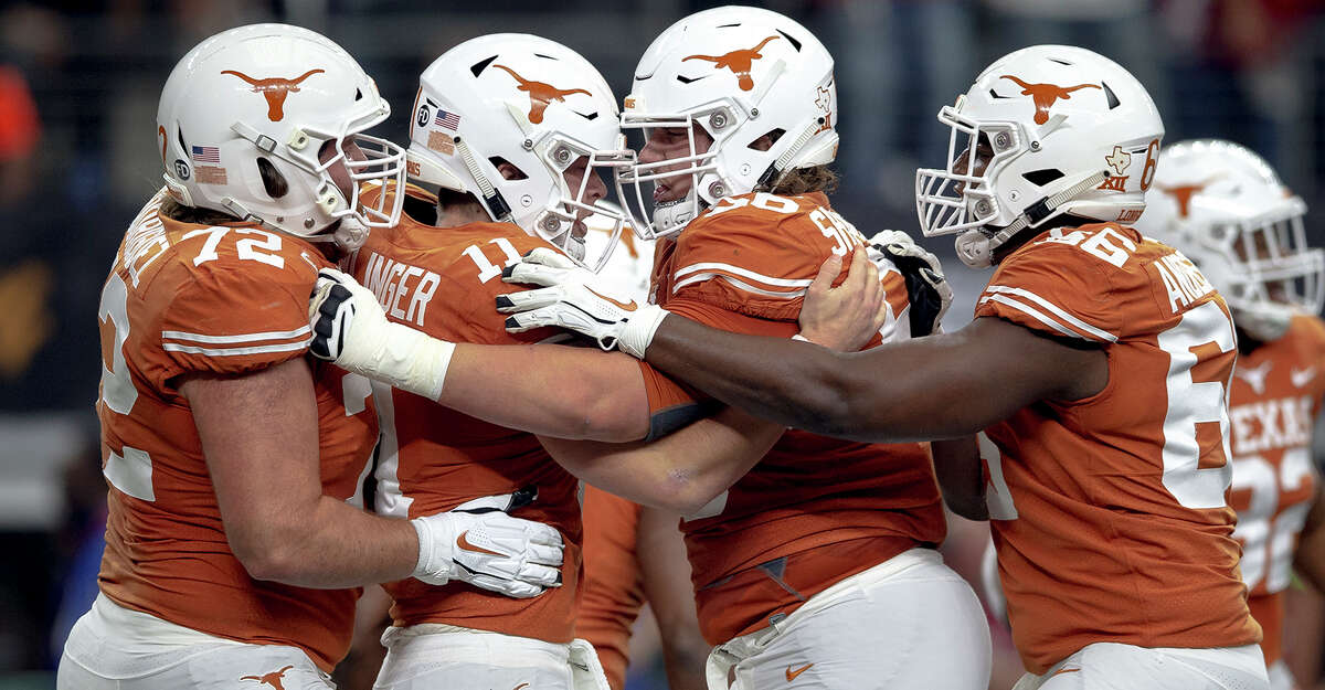 Texas quarterback Sam Ehlinger (11) celebrates his touchdown with teammates during the Big 12 Conference championship NCAA college football game against Oklahoma in Arlington, Texas, on Saturday, Dec. 1, 2018. (Nick Wagner/Austin American-Statesman via AP)