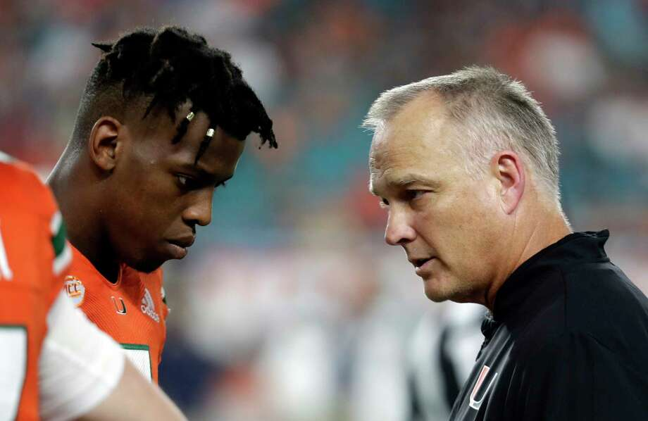 File-This Nov. 24, 2018, file photo shows Miami quarterback N'Kosi Perry, left, talking with Miami head coach Mark Richt during the second half of an NCAA college football game against Pittsburgh, in Miami Gardens, Fla.   The Hurricanes could play the Pinstripe Bowl without Perry in the wake of a sexually explicit video he posted on Snapchat. The video appeared to have been filmed in September but recently resurfaced and could cost Perry (1,089 yards passing, 13 touchdowns) a Pinstripe start. Malik Rosier, who started six games this season before he was replaced by Perry, will likely get the start. Jarren Williams could also get some snaps for the Hurricanes. Richt had not announced a starter on Wednesday. (AP Photo/Lynne Sladky, File) Photo: Lynne Sladky / Copyright 2018 The Associated Press. All rights reserved.