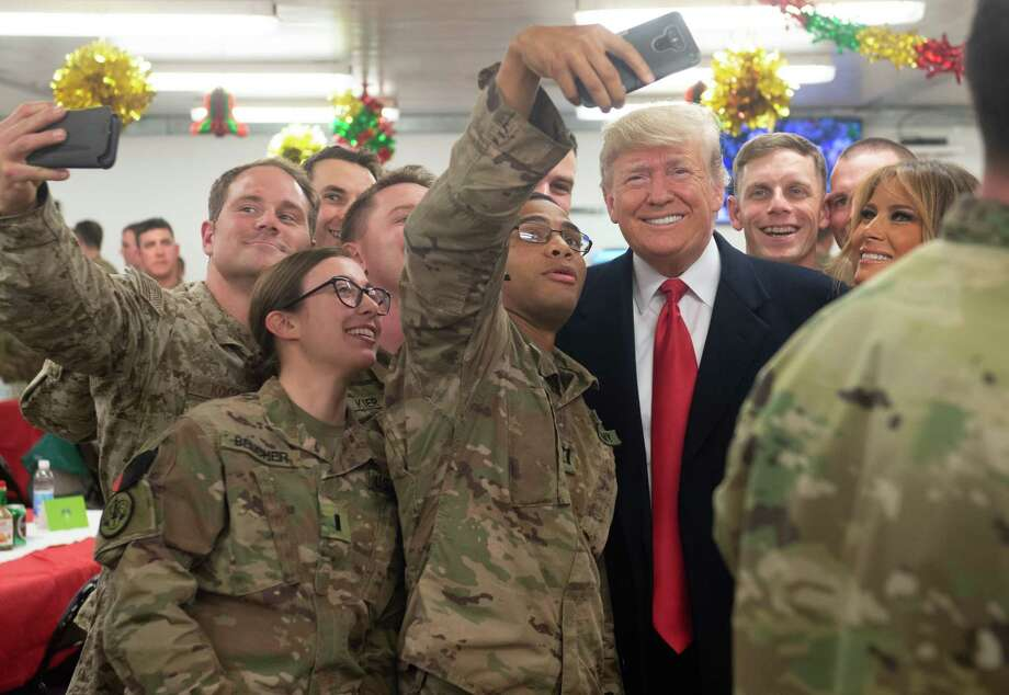 US President Donald Trump and First Lady Melania Trump greet members of the US military during an unannounced trip to Al Asad Air Base in Iraq on December 26, 2018. - President Donald Trump arrived in Iraq on his first visit to US troops deployed in a war zone since his election two years ago (Photo by SAUL LOEB / AFP)SAUL LOEB/AFP/Getty Images Photo: SAUL LOEB / AFP or licensors