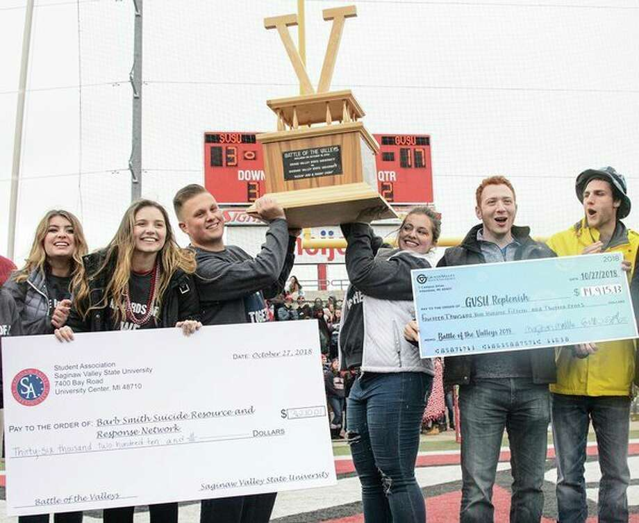 Nolan Twardy and Caitlin Coulter raise 'Victoria,' the traveling trophy that goes to the winner of the annual Battle of the Valleys fundraising competition betweenSaginaw Valley State University and Grand Valley State University, in thisOctober photo. (Photo provided/SVSU)