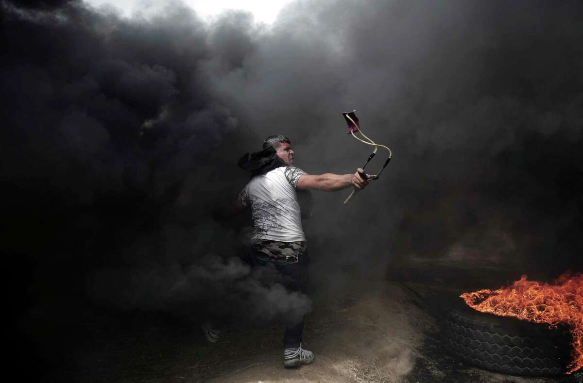 A Palestinian protester hurls stones at Israeli troops during a protest at the Gaza Strip's border with Israel, Friday, April 20, 2018, during a weekly protest on Gaza's border with Israel.