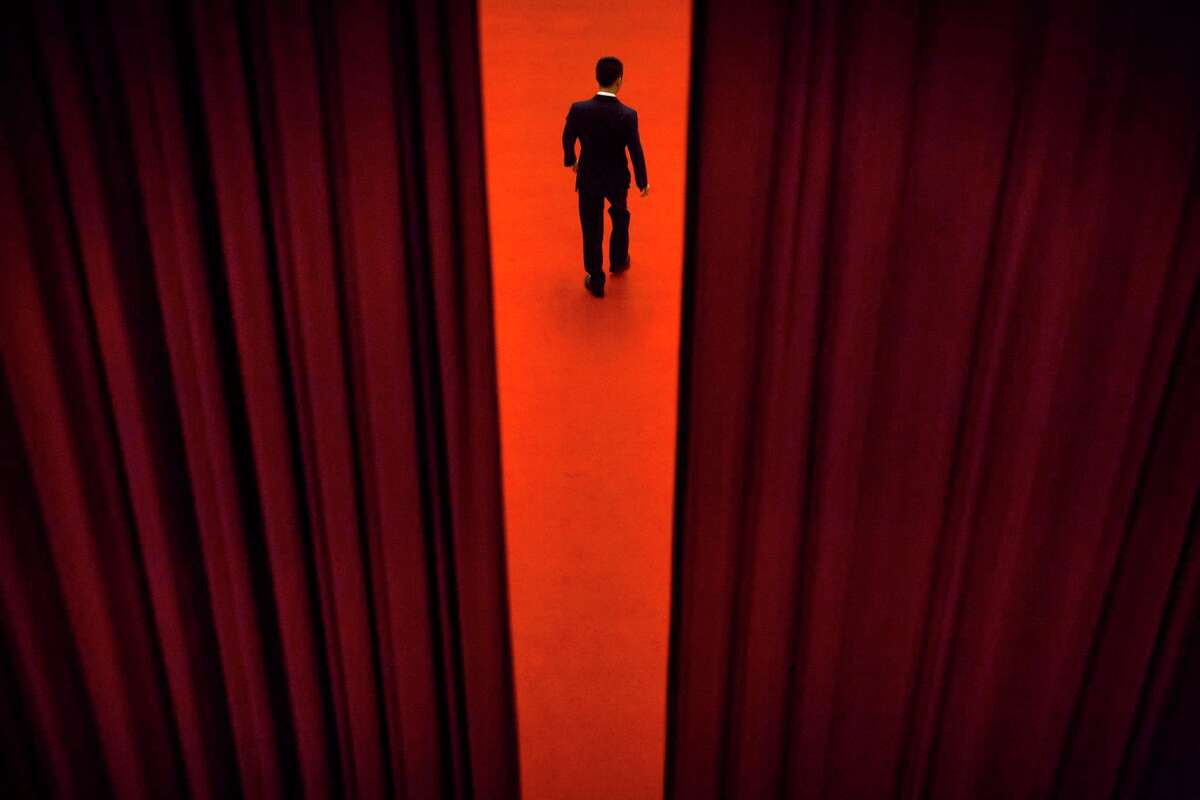 In this Thursday, March 8, 2018 photo, a security official walks through a curtained-off area during a plenary session of the Chinese People's Political Consultative Conference (CPPCC) at the Great Hall of the People in Beijing. The annual conclave of China's National People's Congress is a carefully scripted affair, but the actual decision-making happens out of sight and away from prying eyes.