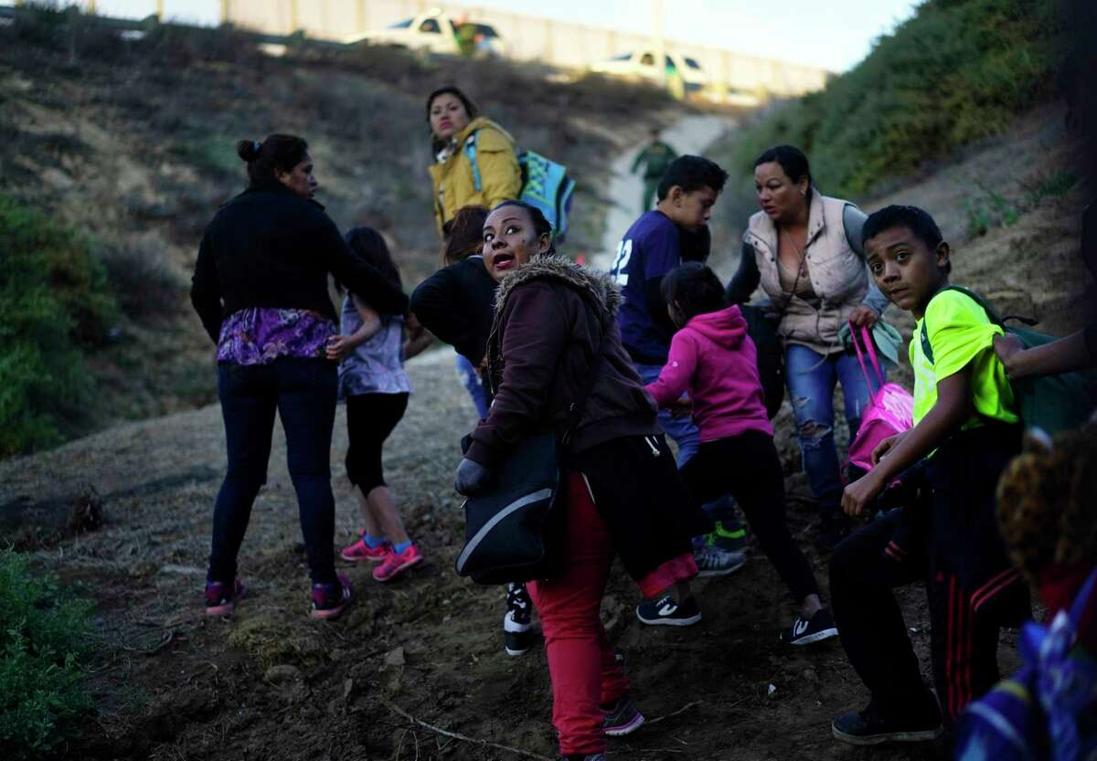 Seen from the Tijuana, Mexico side of the border wall, Honduran migrants who jumped a wall wait on the U.S. side for U.S. Border Patrol agents after surrendering, Sunday, Dec. 2, 2018.