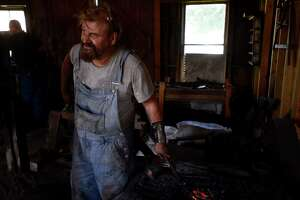 Blacksmith Rob Flurry heats a knife in the fire to harden it during a bladesmithing class at the Spindletop-Gladys City Boomtown Museum on Saturday.  Photo taken Saturday 9/24/16 Ryan Pelham/The Enterprise