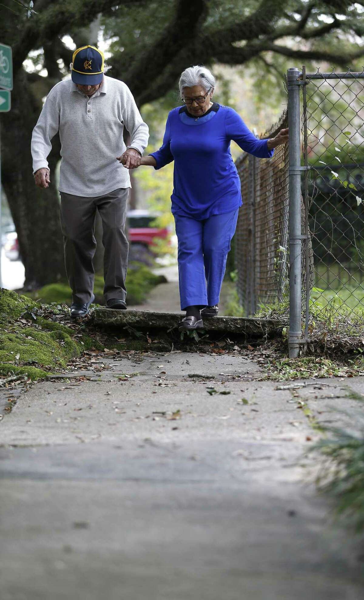 A couple, who did not wish to be identified, carefuly makes their way down a sidewalk, raised up due to tree roots that run under the concrete, on Bayland Street in the Heights.