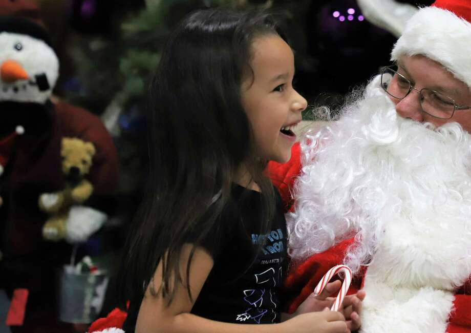 A girl talks to Santa Claus during a Cy-Fair Helping Hands client Christmas event. Photo: Courtesy Of Cy-Fair Helping Hands