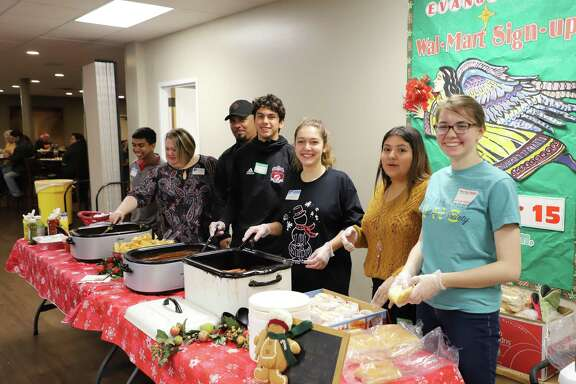 Volunteers for Cy-Fair Helping Hands are ready to serve food.