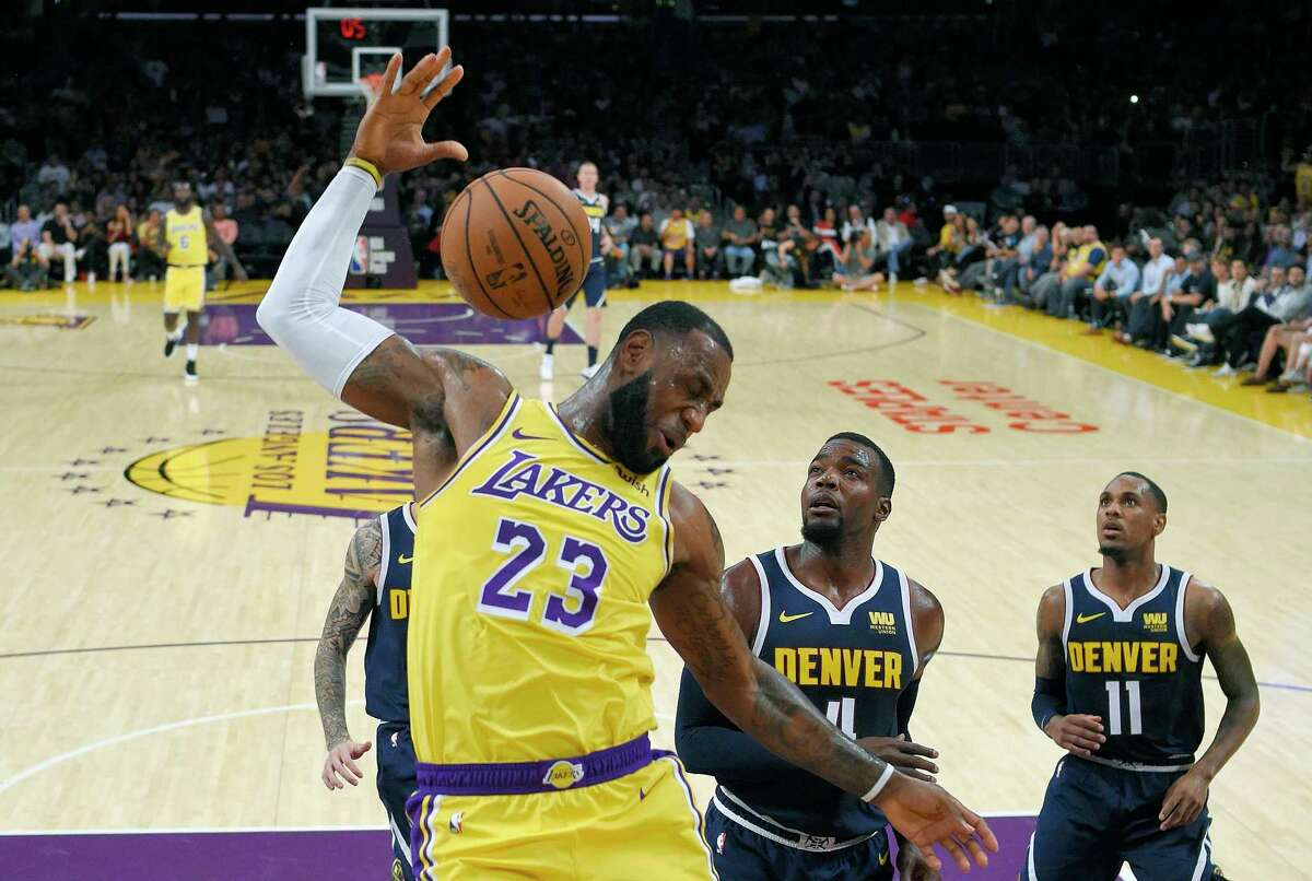 FILE - In this Tuesday, Oct. 2, 2018, file photo, Los Angeles Lakers forward LeBron James, left, follows through on a dunk as Denver Nuggets forward Paul Millsap, center, and guard Monte Morris watch during the first half of an NBA basketball game in Los Angeles. LeBron James was named The Associated Press Male Athlete of the Year on Thursday, Dec. 27, 2018.