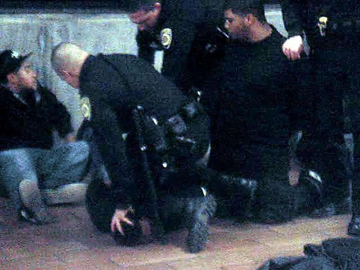 An image from a video of the 2009 BART police shooting of Oscar Grant at Fruitvale Station in Oakland shows the scene just moments before former Officer Johannes Mehserle shot Grant. Former Officer Anthony Pirone can be seen holding Grant's head down with his left hand, with his left knee on Grant's neck. Mehserle is bent over, about to fire his pistol. Two of Grant's friends look on.