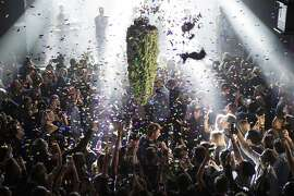 FILE - In this Oct. 17, 2018, file photo a depiction of a cannabis bud drops from the ceiling at Leafly's countdown party in Toronto as midnight passes and marks the first day of the legalization of cannabis across Canada. The last year was a 12-month champagne toast for the legal marijuana industry as the global market exploded and cannabis pushed its way further into the financial and cultural mainstream. Canada ushered in broad legalization, U.S. drug regulators approved the first cannabis-based drug and investors pumped in billions of dollars. (Chris Young/The Canadian Press via AP, File)