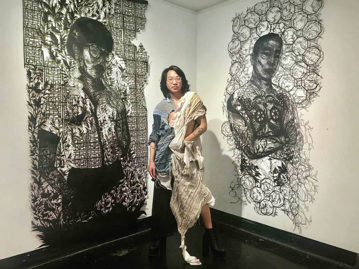 The artist Antonius Bui with two of his large cut-paper portraits, on view in his show yeu em dai lau (me love you long time), on view at Lawndale Art Center through March 3.