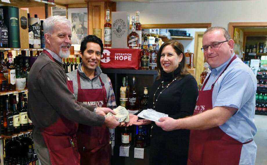 "From left, Harry's Wine & Liquor Market co-owner Patrick Monteleone, artisan beer specialist Renzo Kian-Kubota, Operation Hope of Fairfield Executive Director Carla Miklos and Harry's co-owner William Miller hold proceeds from the shop's Rare Bottles"" fundraiser in October. The money was given to Operation Hope to support ts efforts to end hunger and end homelessness in the local community. Photo: Contributed Photo"
