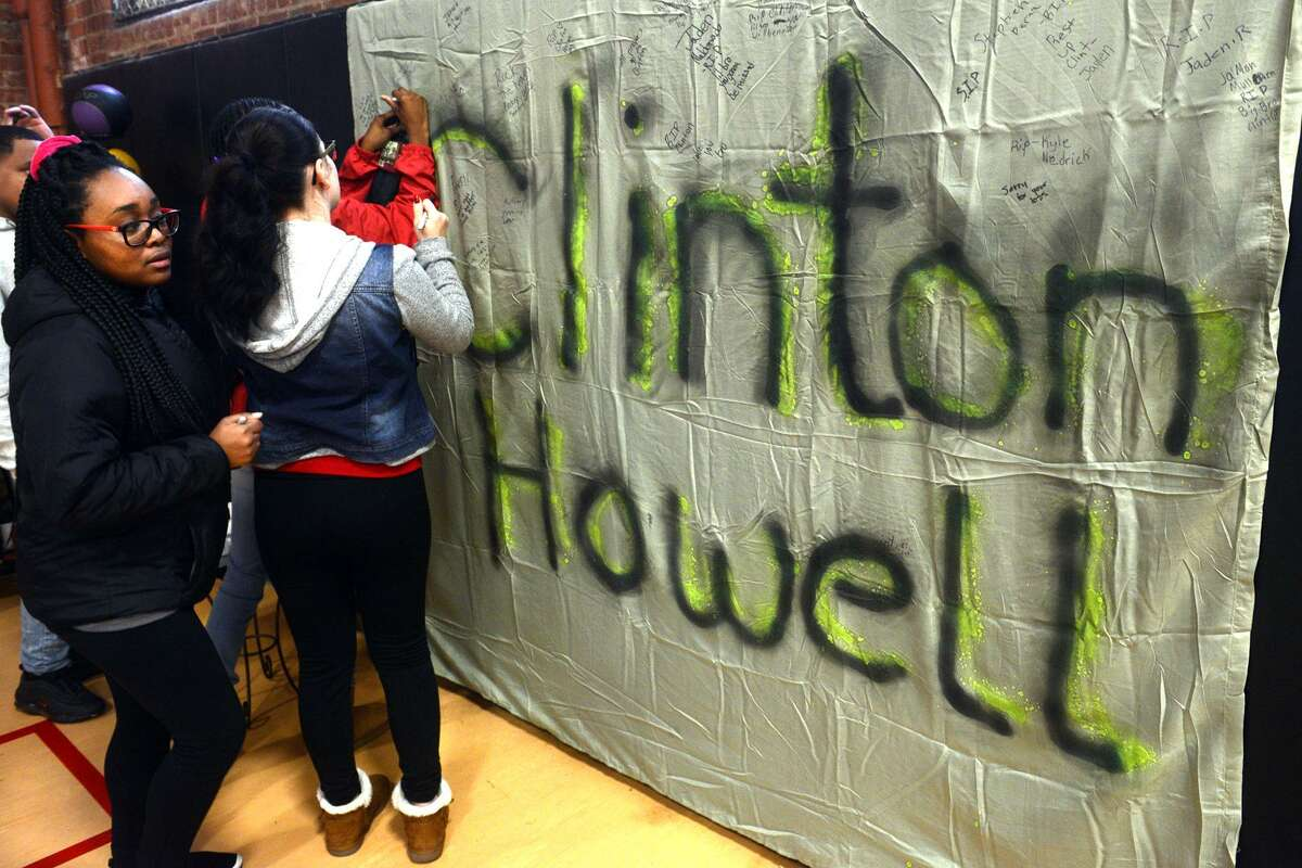 Students sign a banner in honor of Clinton Howell prior to a Celebration of Life service held at The Bridge Academy, in Bridgeport, Conn. Dec. 21, 2018. Howell, 12, a 7th grader at the school, was killed by gunfire outside his home Tuesday evening.