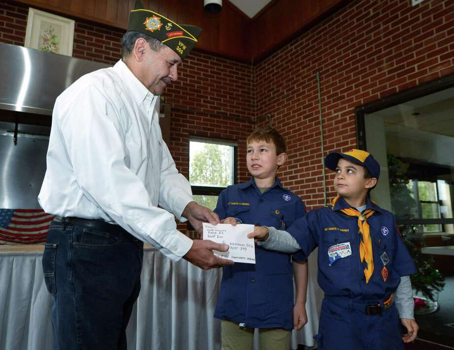 Cub Scout Pack 39 Wolf Den including Austin Charice and John Weddle, right, present money raised from a community service project to the local VFW Post 399 Commander Bernie Rombout on Saturday in Westport. The Pack 39 scouts collected aluminum cans to raise nearly $100 for the project. It will go toward the purchase of service dogs for disabled veterans. Photo: Erik Trautmann / Hearst Connecticut Media / Norwalk Hour