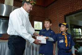 Cub Scout Pack 39 Wolf Den including Austin Charice and John Weddle, right, present money raised from a community service project to the local VFW Post 399 Commander Bernie Rombout on Saturday in Westport. The Pack 39 scouts collected aluminum cans to raise nearly $100 for the project. It will go toward the purchase of service dogs for disabled veterans.