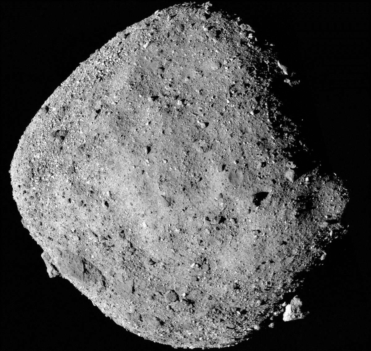 FILE - This mosaic image composed of 12 PolyCam images collected on Dec. 2, 2018, and provided by NASA shows the asteroid Bennu. NASA's first look at a tiny asteroid shows the space rock is more moist and studded with boulders than originally thought. Scientists on Monday, Dec. 10, released the first morsels of data collected since their spacecraft Osiris-Rex hooked up last week with the asteroid Bennu, which is only about three blocks wide and weighs about 80 million tons (73 million metric tons). Bennu regularly crosses Earth's orbit and will come perilously close to Earth in about 150 years. (NASA/Goddard/University of Arizona via AP)