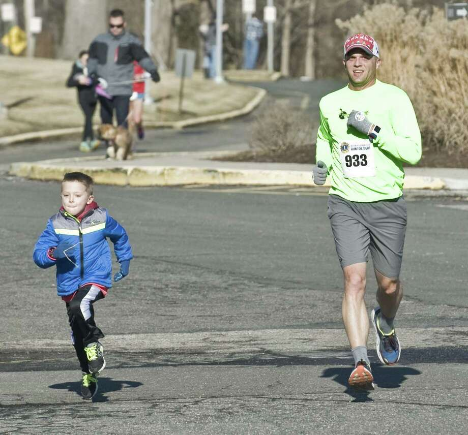 Jack Pierz, 6 of Brookfield, joins his dad, John, for the last leg of the 30th Brookfield Lions Run for Sight at Brookfield High School. Sunday, Jan. 1, 2017 Photo: Scott Mullin / For Hearst Connecticut Media / The News-Times Freelance