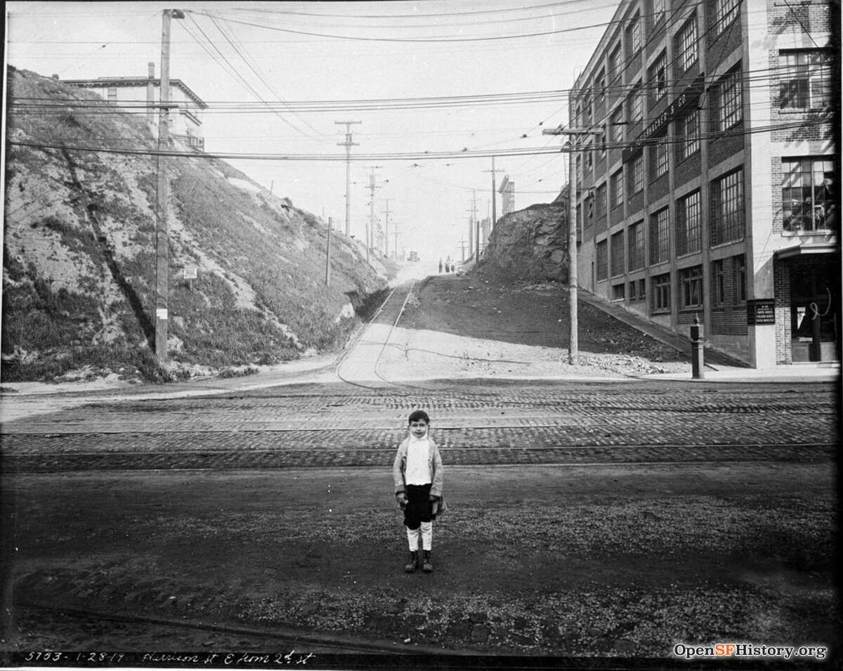 The view east on Harrison from 2nd in San Francisco, with a boy wearing an influenza mask pulled down. The A. Fleishhacker and Company warehouse is at right. Credit: OpenSFHistory