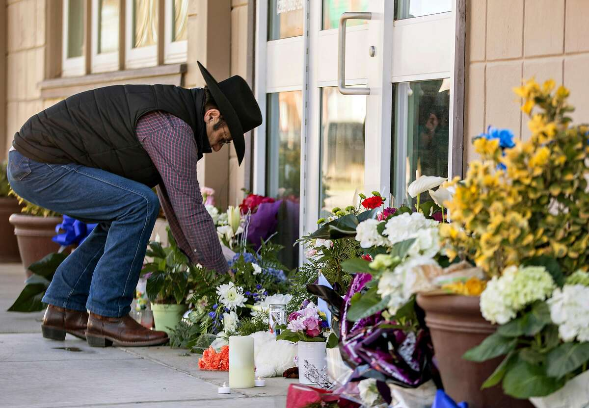 Newman resident Sal Ramirez places flowers at a growing memorial outside of the Newman Police Department in Newman, Calif. Thursday, Dec. 27, 2018 after Newman Police Officer Ronil Singh was shot and killed early Wednesday morning during a traffic stop.