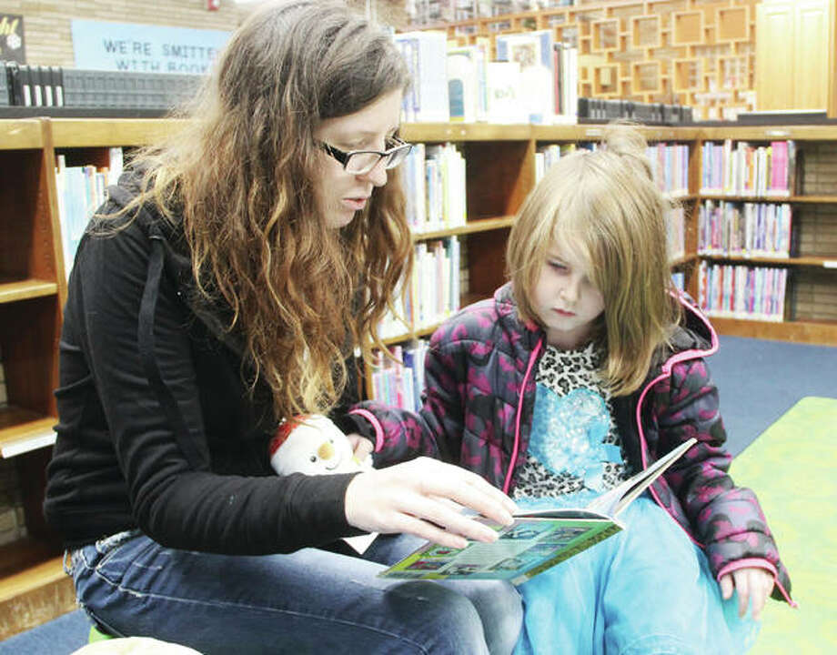"""Ashley Huether reads to her daughter, Ember, 5, during a """"stuffed animal sleepover"""" at the Wood River Public Library Thursday."""