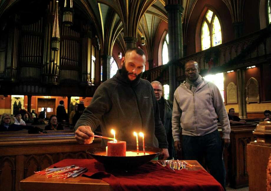 John Freitas, of New Haven, lights a candle in memory of a homeless friend of his who died, during the 3rd Annual Homeless Memorial Service at Trinity Church on the Green in New Haven, Conn., on Thursday, Dec. 27, 2018. The service was held to remember 24 homeless people who died in 2018. Photo: Christian Abraham / Hearst Connecticut Media / Connecticut Post