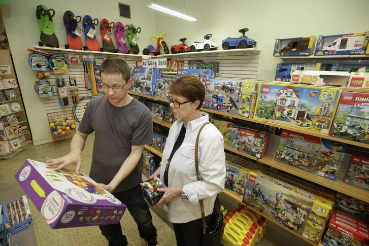 Cliff Moss, manager, left, helps customer Sue McFarland, right, at FUNdamentally Toys, 2401 Rice Blvd., Thursday, Dec. 27, 2018, in Houston.