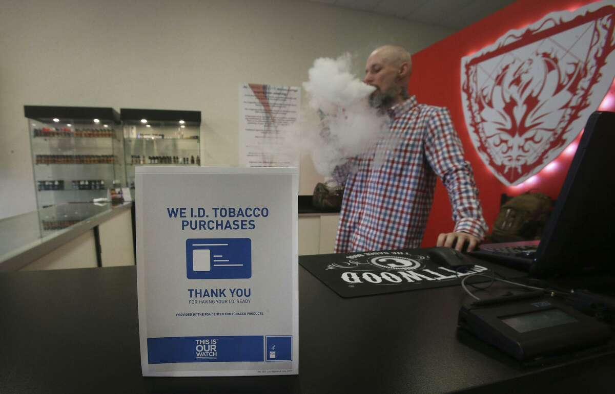 FILE - A sign on the counter at the Smoke to Live vape shop in San Antonio, Texas. Monday, the Texas Senate will hear state bill aimed to raise the purchasing age of all tobacco products, including cigarettes and e-cigarettes.