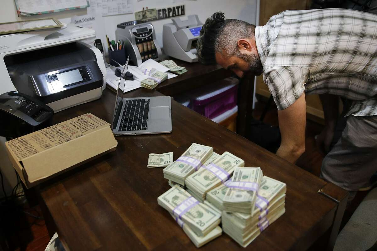 FILE - In this June 27, 2017, file photo, bundles of $20 bills are placed on a table as Jerred Kiloh, owner of the Higher Path medical marijuana dispensary, prepares a trip to Los Angeles City Hall to pay his monthly tax payment in cash in Los Angeles. California would likely lose money and face insurmountable federal hurdles if it tried to create a state-backed bank for the marijuana industry. That's according to a report released Thursday, Dec. 27, 2018, by state Treasurer John Chiang. It puts an end for now to hopes of creating a public bank as California's recreational marijuana market concludes its first year. Chiang is blasting the federal government for keeping marijuana a Schedule 1 drug even though 33 states have legalized it for recreational or medicinal purposes. (AP Photo/Jae C. Hong, File)