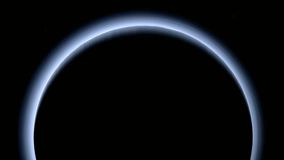 FILE - This image made available by NASA in March 2017 shows Pluto illuminated from behind by the sun as the New Horizons spacecraft travels away from it at a distance of about 120,000 miles (200,000 kilometers). The probe will ring in 2019 by exploring an even more distant and mysterious world. (NASA/Johns Hopkins University Applied Physics Laboratory/Southwest Research Institute via AP) / NASA