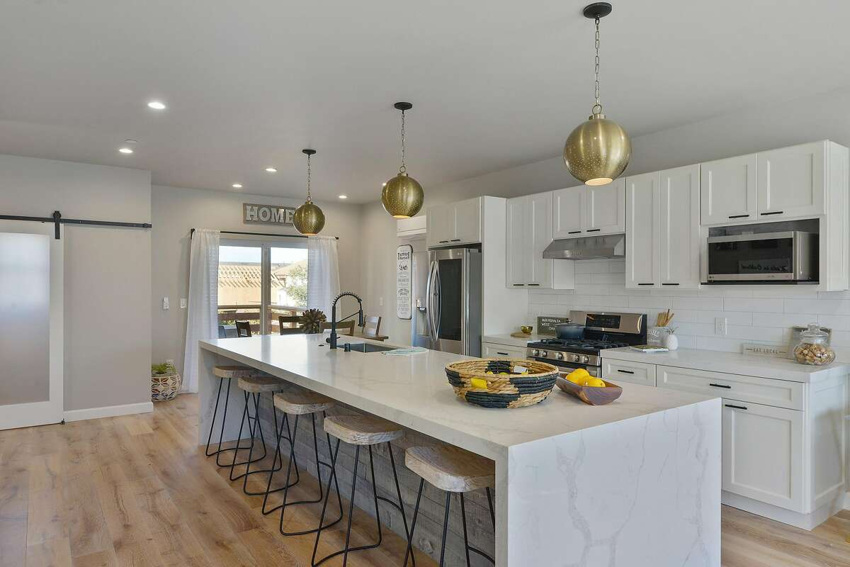 The great room hosts a chef's kitchen with stainless steel appliances and a dining area that steps out to a covered deck.