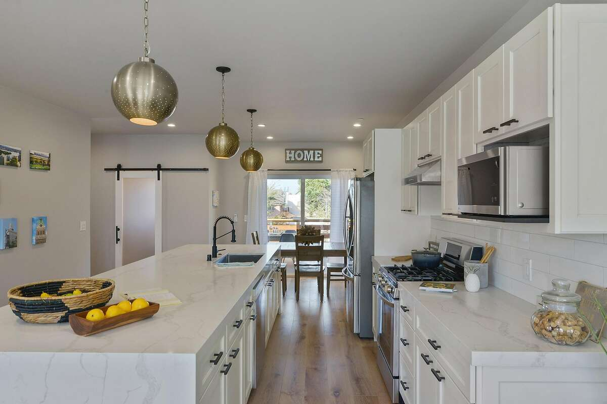 The open kitchen enjoys quartz counters and a waterfall island that seats six.