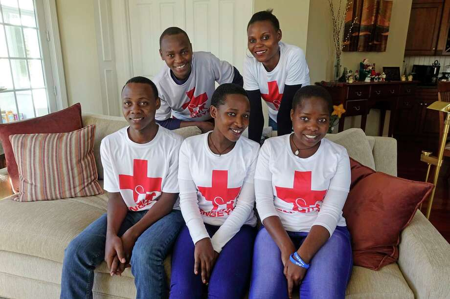 Students from Uganda, left to right, Hamuza Mugisha, Wilbur Bongole, Josephine Nakate, Susan Nabukenya, and Harriet Nakajimu, all part of the Engeye Scholar's Program, pose for a photo at the home of Elaine Pers Hickey on Thursday, Dec. 20, 2018, in Watervliet, N.Y. Pers Hickey along with Theresa Weinman founded the Engeye Scholar's Program.  (Paul Buckowski/Times Union) Photo: Paul Buckowski / (Paul Buckowski/Times Union)