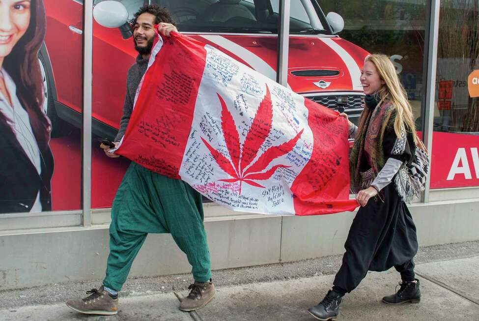 FILE - In this Oct. 17, 2018, file photo, people hold up a Canadian flag with a marijuana logo on it outside a government cannabis store in Montreal. California became America?'s largest legal marketplace in 2018, while Canada became the second and largest country with nationwide legal recreational marijuana. (Graham Hughes/The Canadian Press via AP, File)