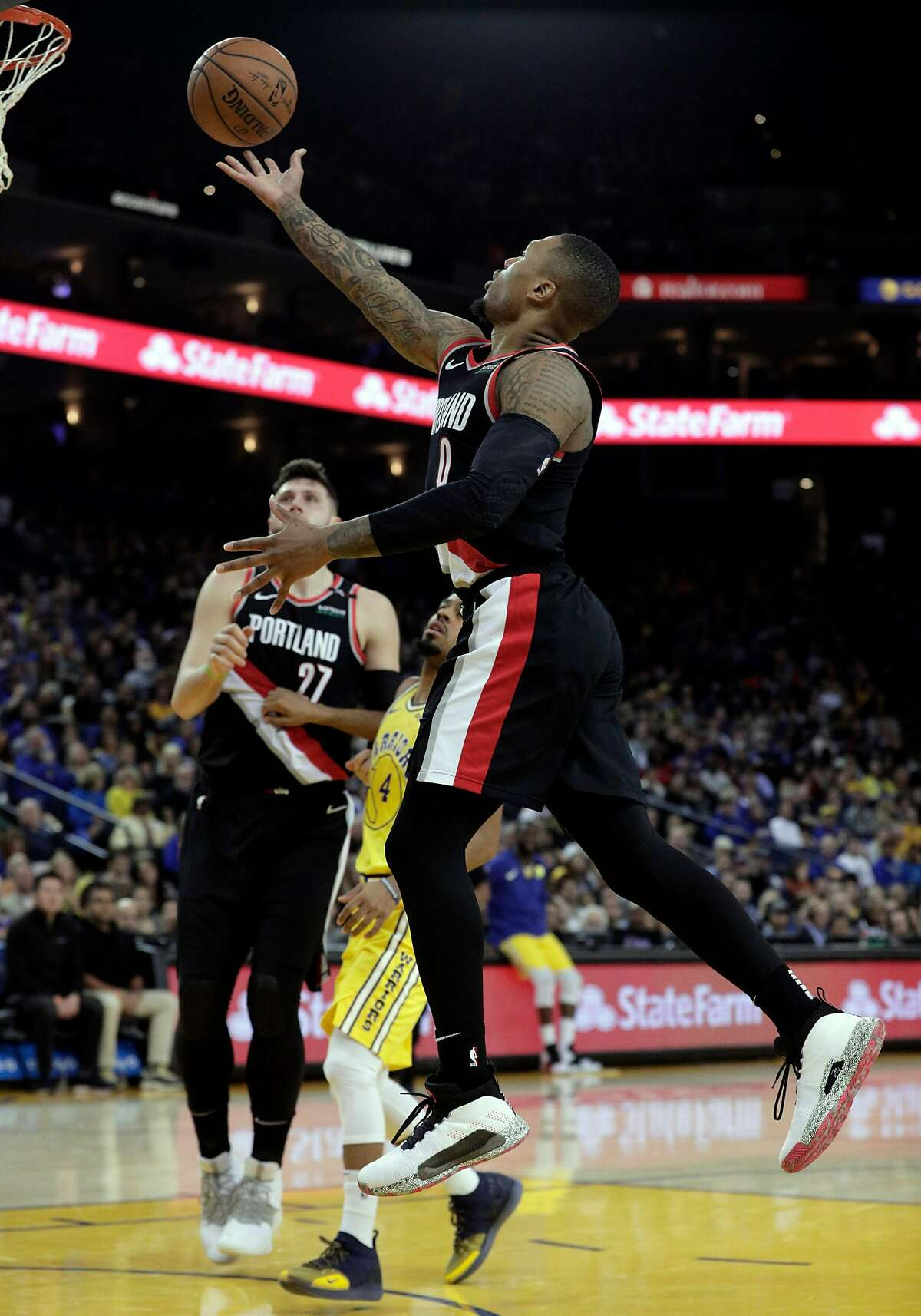 Damian Lillard (0) floats in a layup in the first half as the Golden State Warriors played the Portland Trailblazers at Oracle Arena in Oakland, Calif., on Thursday, December 27, 2018.