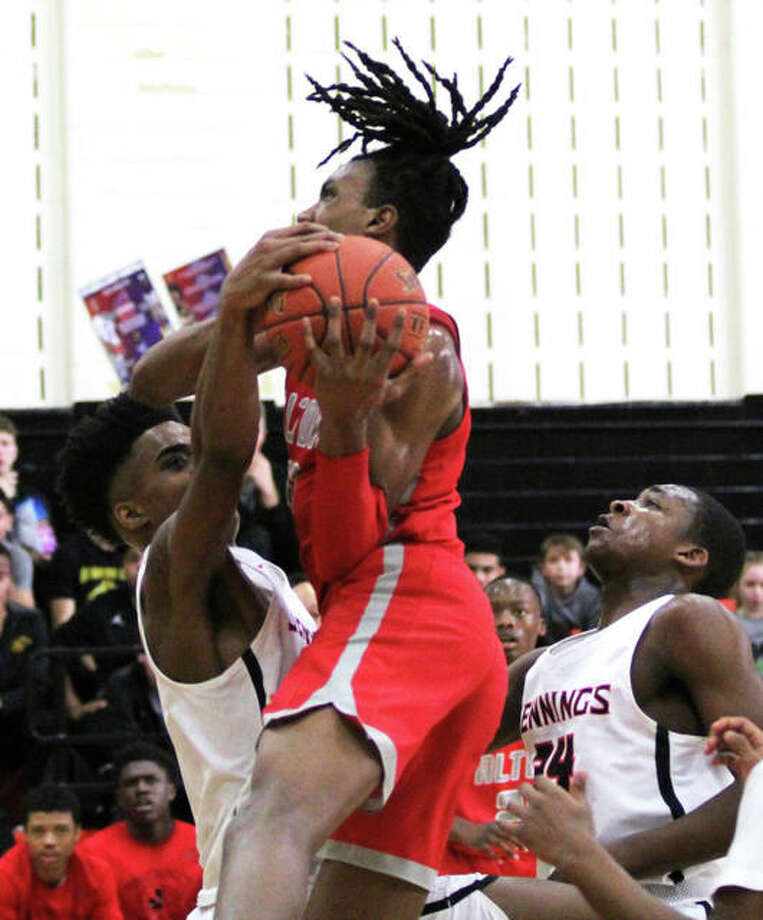 Alton's Donovan Clay (middle) goes up for a shot against Jennings in a shootout at Webster Groves on Dec. 15. Clay scored 19 points in the Redbirds' victory Thursday at the Centralia Tournament. Photo: Greg Shashack / The Telegraph