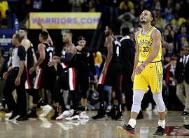 Stephen Curry (30) walks back to the bench after Damian Lillard (0) scored a three pointer to put Portland ahead in the overtime period as the Golden State Warriors played the Portland Trailblazers at Oracle Arena in Oakland, Calif., on Thursday, December 27, 2018.