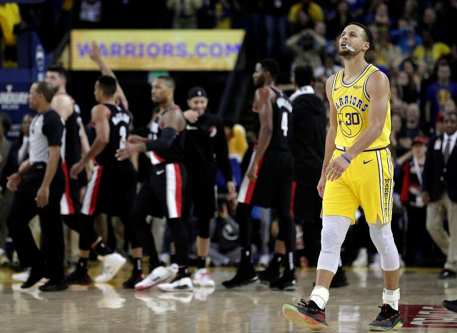 Stephen Curry (30) walks back to the bench after Damian Lillard (0) scored a three pointer to put Portland ahead in the overtime period as the Golden State Warriors played the Portland Trailblazers at Oracle Arena in Oakland, Calif., on Thursday, December 27, 2018. Photo: Carlos Avila Gonzalez / The Chronicle