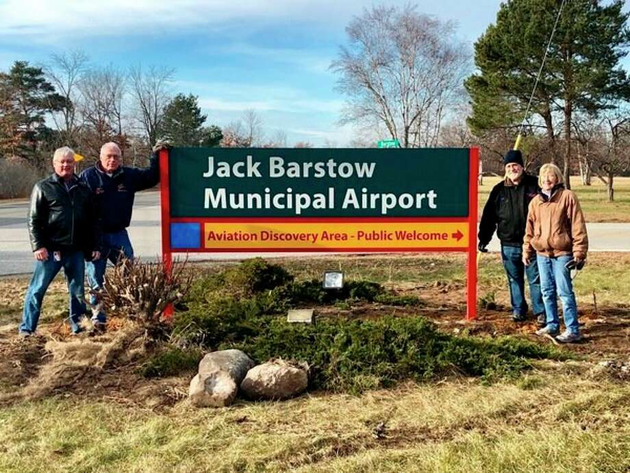 Four members of the Midland Aviation Education Association stand beside the new Jack Barstow Airport sign.From left areJim Cordes, Matt Janson, John Swantek and Dot Hornsby. (Submitted photo)
